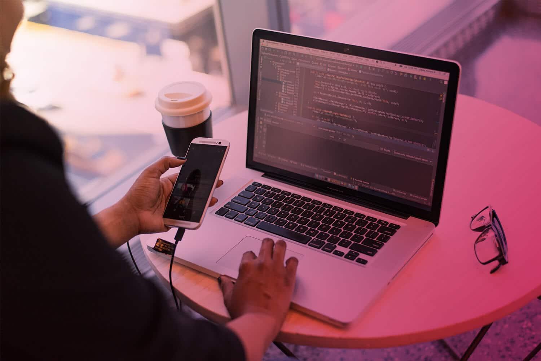Zum Thema App Entwicklung: Laptop, Smartphone, App Entwickler am Schreibtisch