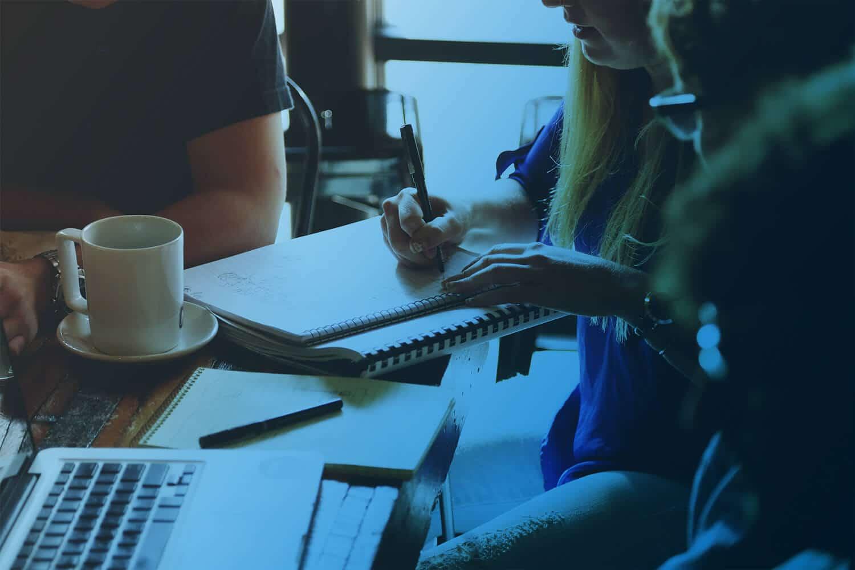 Zum Beitrag IoT POC: Menschen am Schreibtisch, Laptop, Tasse, Block