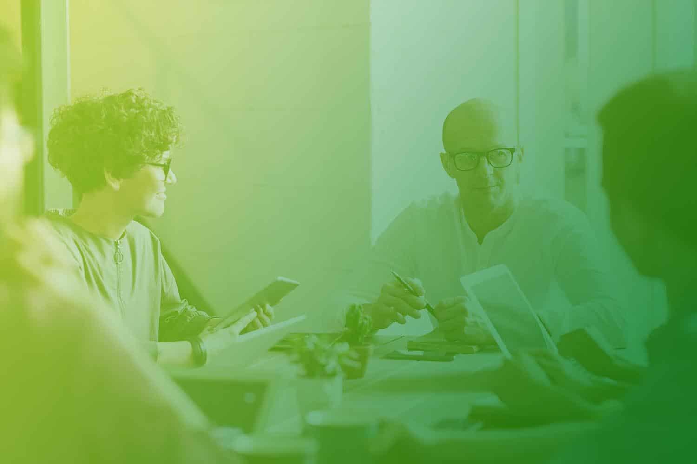 Zum Beitrag App Entwicklung - 10 Dinge die du beachten musst: Menschen am Tisch mit Smartphone, Tablet, Stift