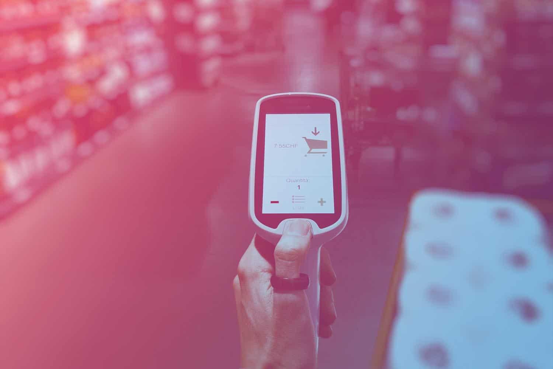 Zum Beitrag Iot im Handel: Barcode Scanner in der Hand, Regale im Supermarkt