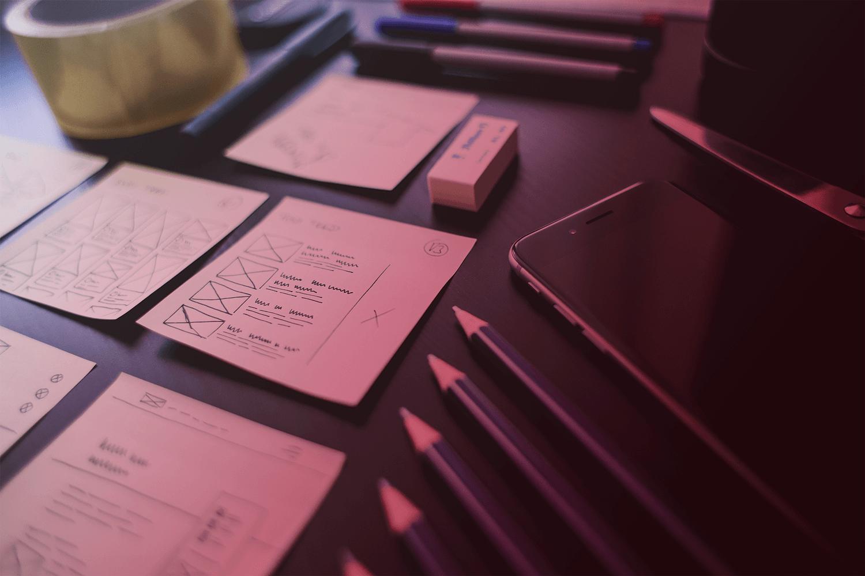 Zum Thema Rapid Prototyping in der Softwareentwicklung: Tisch mit Sketches, Bleistiften, Smartphone, Radiergummi, Schere, Stifte