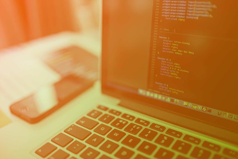Zum Beitrag Low Code - Nachhaltige IoT Lösungen für den Mittelstand: Laptop mit Code, Smartphone