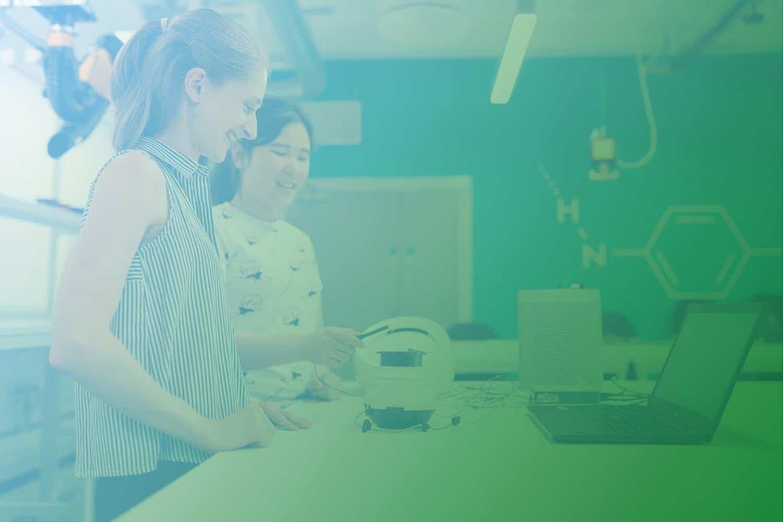 Produktdigitalisierung ist in Zeiten des Internet der Dinge in vielen Unternehmen notwendig: Zwei Frauen stehen an einem Tisch mit Laptop und Gerät