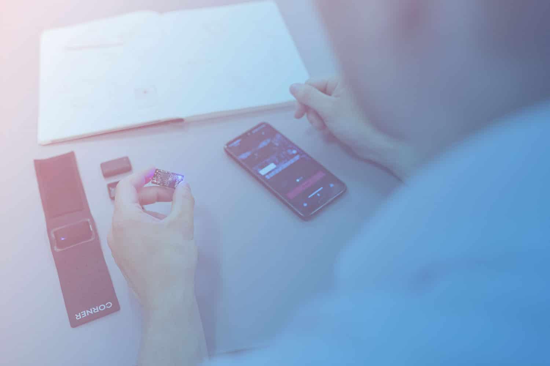 Mann bei der App Entwicklung mit dem Smartphone auf dem Tisch und IoT-Hardware in der Hand