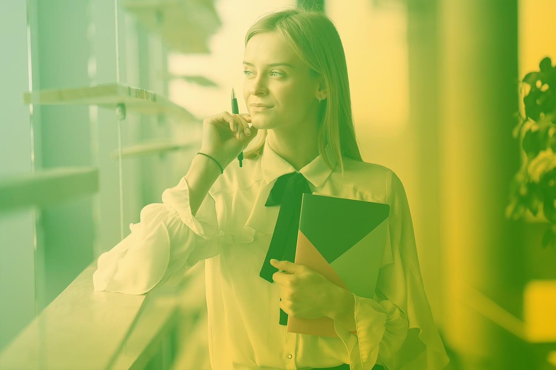 Zum Artikel So prüfst Du die Machbarkeit Deiner IoT Produktidee: Frau mit Block und Stift in der Hand guckt aus dem Fenster
