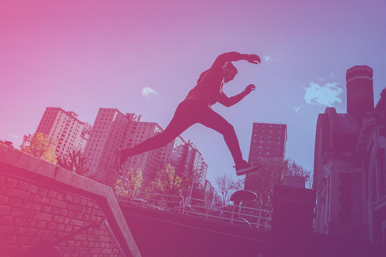 """Zum Beitrag """"IoT-Projekte scheitern - das kannst du tun"""": Mann springt von Mauer. Im Hintergrund sind Häuser."""