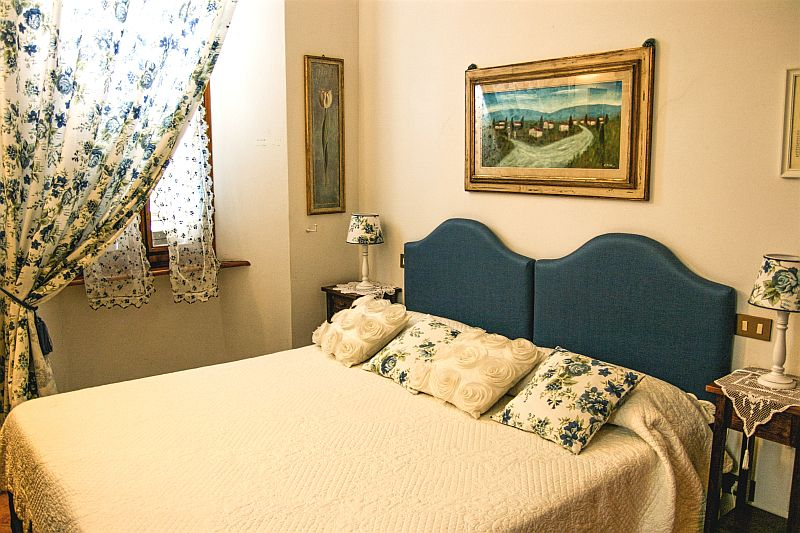 a bed with a white cover and cushions with blue flowers in a hotel room, curtains with flowers and a painting