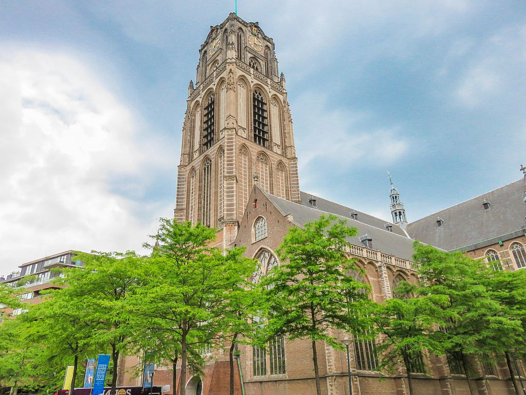 a Gothic church with some green trees in front, the Laurens Church in Rotterdam