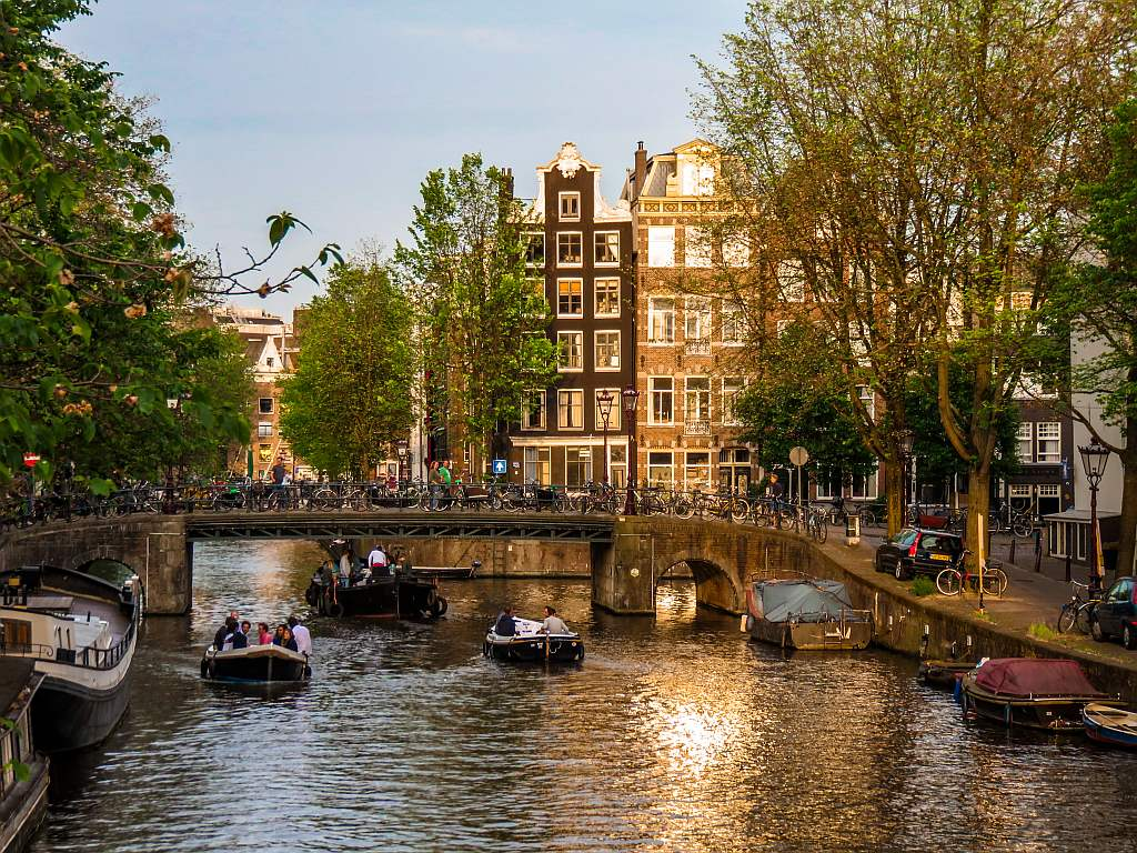 a canal with a bridge and boats in the canal, Amsterdam the Nehterlands