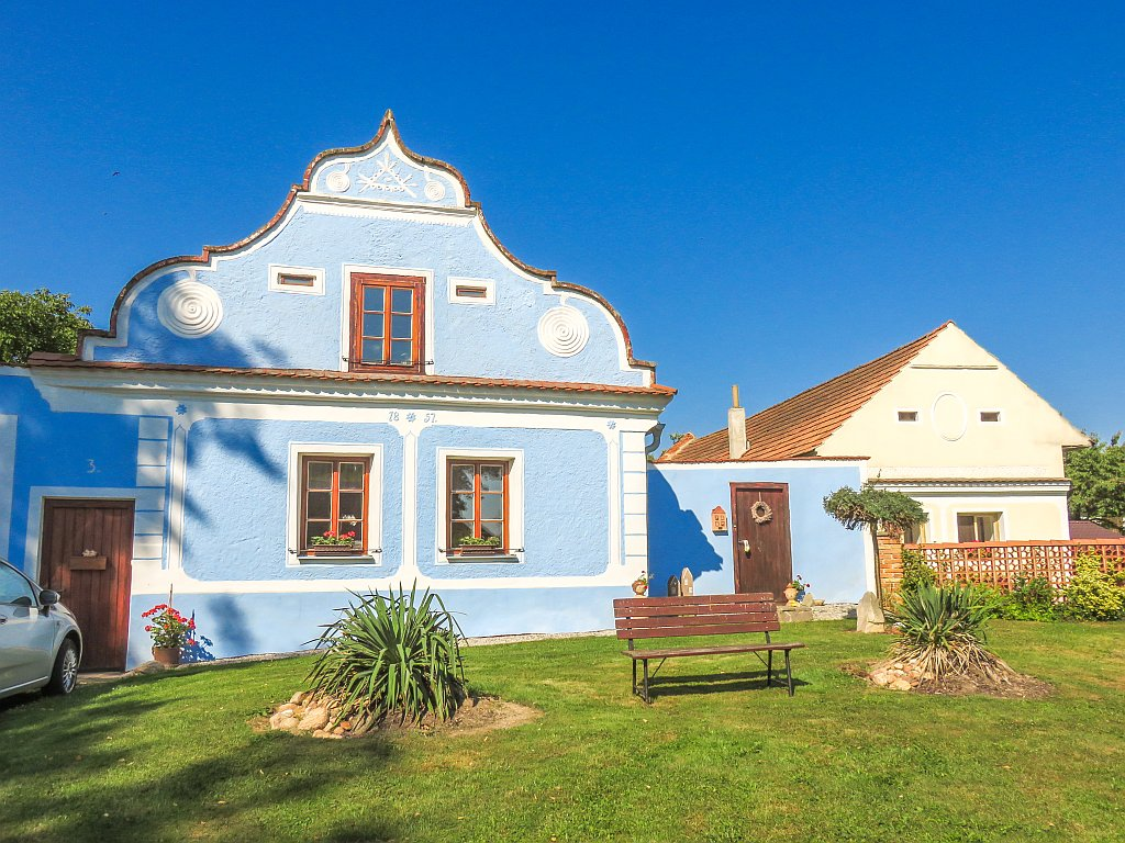 a blue house with white ornaments on the facade in rural Baroque style, a house in Male Hrastany in South Bohemia, Czech Republic