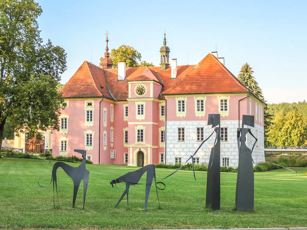 a reddish castle with yellow ornaments around the windows at the background, in front an artsy metal sculpture of two ladies walking two dogs, Mitrovicz Castle in South Bohemia, Czech Republic