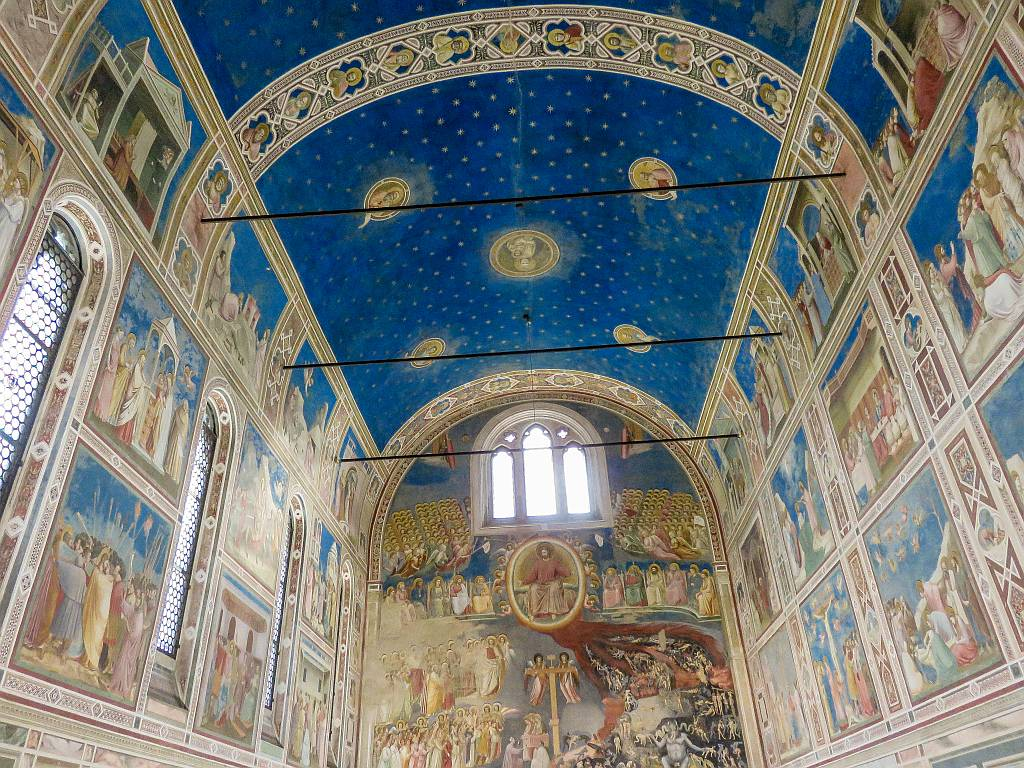 an interior of a church all frescoed in blue colour, the interior of the Scrovegni Chapel in Padua