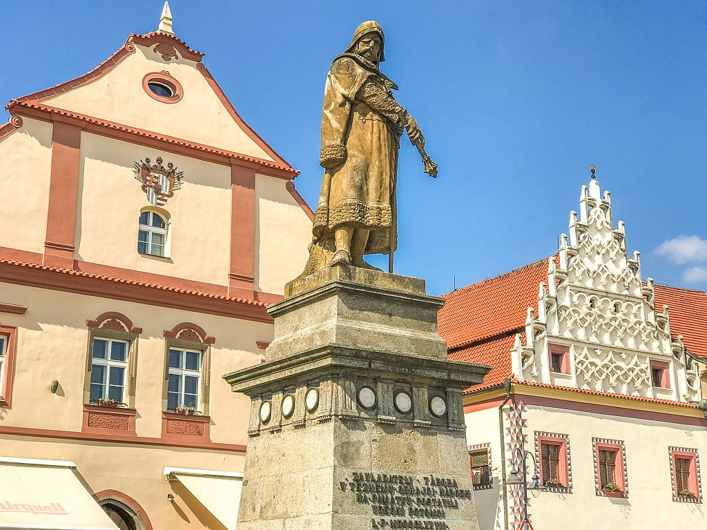a monument of a person in front of an orange building with red decorations, Tabor