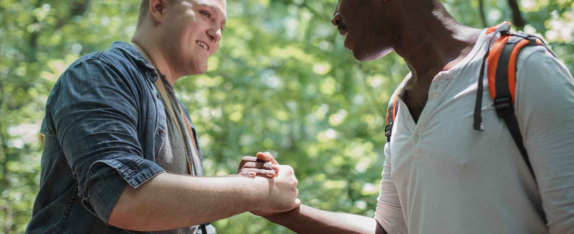 positive multiethnic men shaking hands in forest