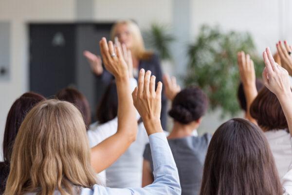 Group of businesswomen attending a seminar, raising their hands. Focus on hands.