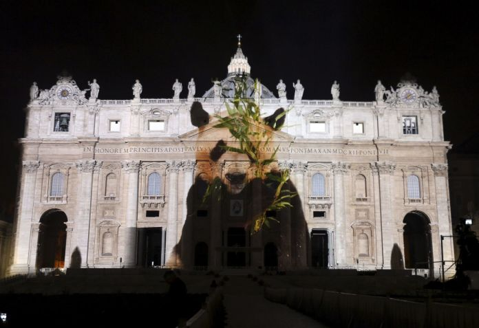 """A picture of a panda, part of an art projection featuring images of humanity and climate change artistically rendered by Obscura Digital, is projected onto the facade of St. Peter's Basilica, as part of an installation entitled """"Fiat Lux: Illuminating our Common Home"""" as a gift to Pope Francis on the opening day of the Extraordinary Jubilee, at the Vatican, December 8, 2015. REUTERS/Stefano Rellandini FOR EDITORIAL USE ONLY. NO RESALES. NO ARCHIVE. - RTX1XT46"""