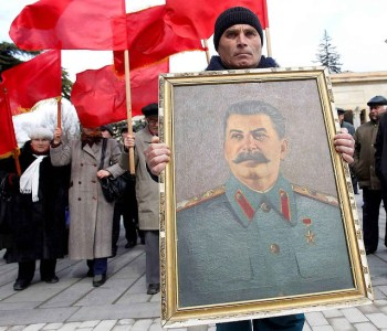 People carry red flags and a portrait of the late Soviet leader Josef Stalin during a ceremony to mark the 60th anniversary of his death in his hometown of Gori, about 80 km (50 miles) west of Georgia's capital Tbilisi March 5, 2013. REUTERS/David Mdzinarishvili (GEORGIA - Tags: POLITICS ANNIVERSARY SOCIETY)