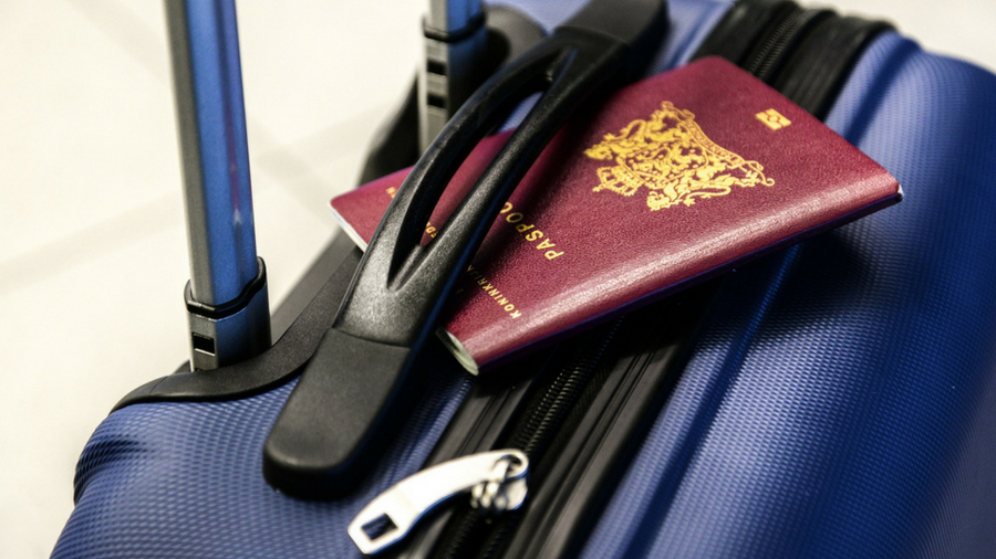 Image of a passport on top of a suitcase
