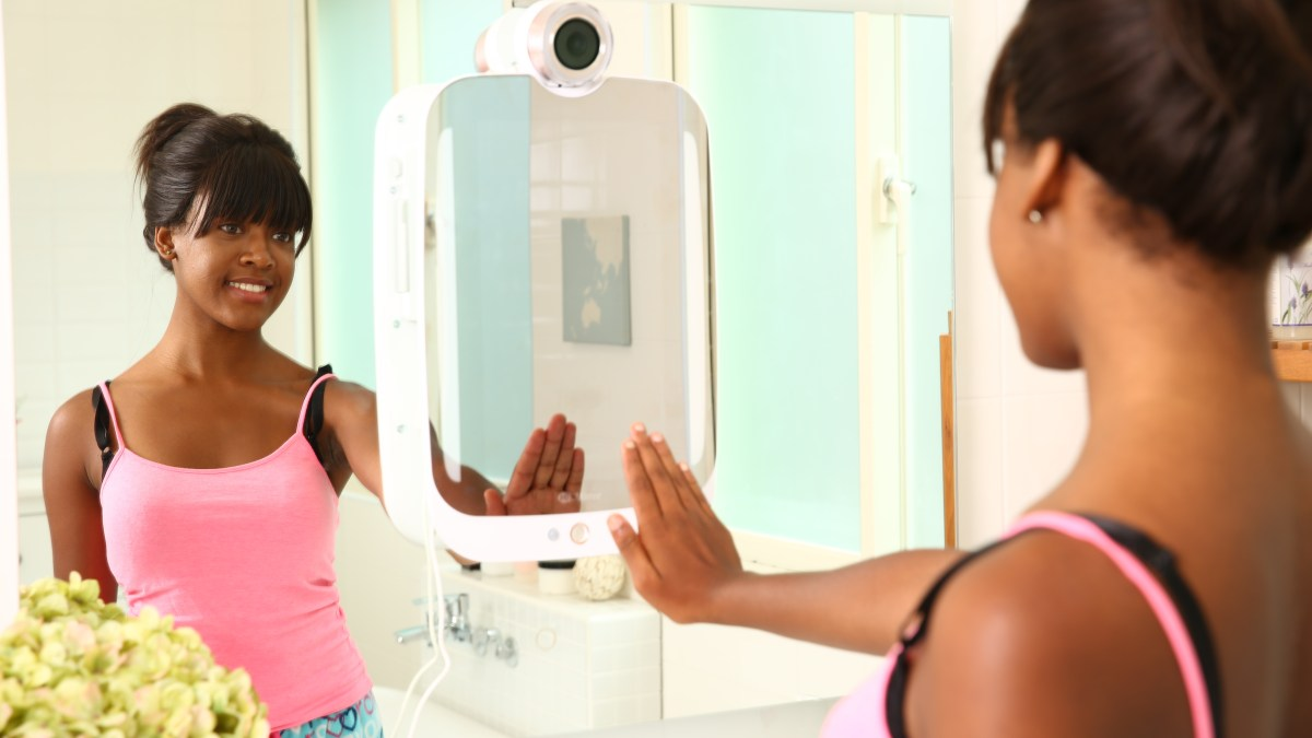 Smiling young woman in front of smart mirror