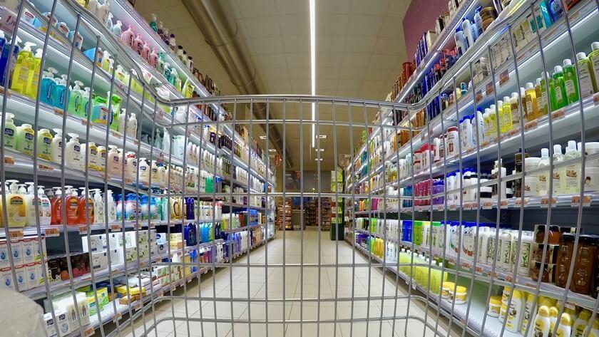 koszyk na zakupy między regałami w supermarkecie