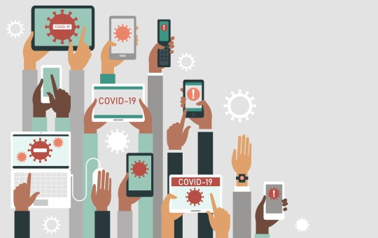 Panic of COVID-19 outbreak concept. Human hands holding various smart devices with coronavirus alerts on their screens.