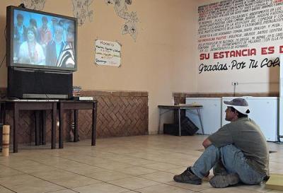 Mariano, un migrante de Honduras, mira television en Belen, Posada del Migrante. Foto de LatinDispatch.