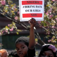 Boy holds sign to bring our girls back at rally