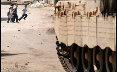 Palestinian children run across a road in front of an advancing Israeli tank.