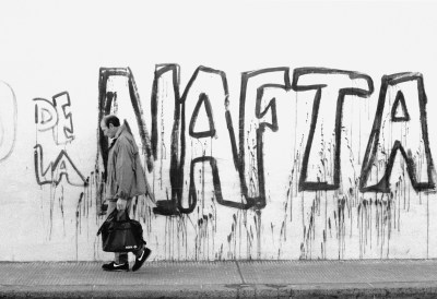 man in nikes in front of NAFTA graffiti