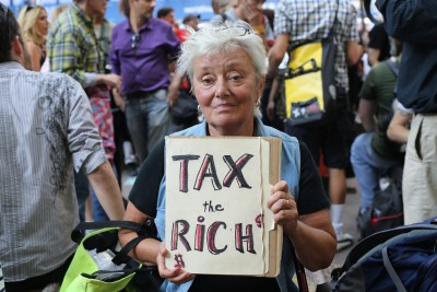 person-holding-tax-the-rich-sign-protest