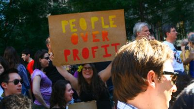 woman holding a sign that reads people over profit in regard to the coronavirus stimulus bill
