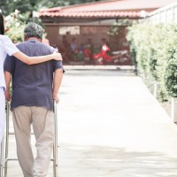 caregiver helping a patient use walker