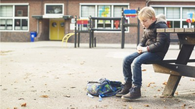 A student sits on a bench at an empty school.