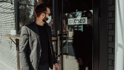 person walking during the coronavirus looking at closed business