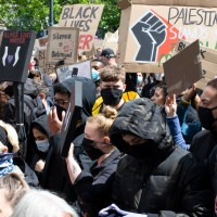 Manchester UK. June 6 2020. Black Lives Matter protest in Piccadilly Gardens. Large crowd march with cardboard placards in front of city shops