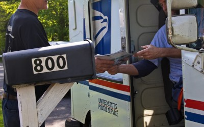 Postal worker hands a man his mail