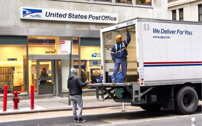 USPS postman on a mail delivery truck in New York. USPS is an independent agenc of US federal government responsible for providing postal service in the US