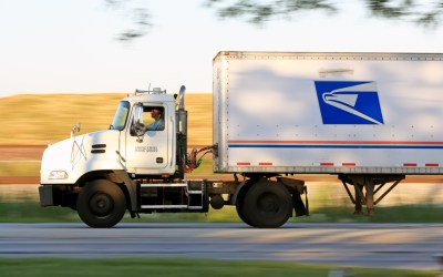 postal service worker driving a delivery truck