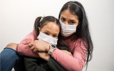 Latina mother and daughter hug each other and wearing medical masks for fear of COVID-19