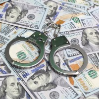 money and handcuffs to depict tax avoidance - taxation - tax evasion