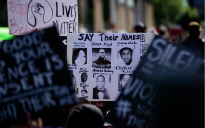 protest sign showing the faces of people police kill