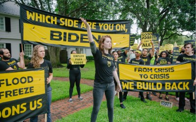 activists with sunrise movement stand with protest signs