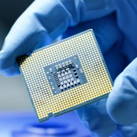 gloved hand holding semiconductor chip