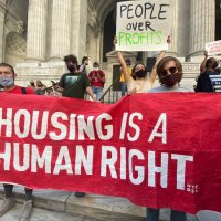 advocates holding sign that says housing is a human right