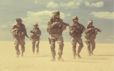 u.s. military soldiers armed and patrolling a sandy aread resembling a desert