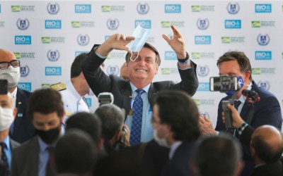 Brazilian president jair Bolsonaro holds a mask as waves to the followers during a ceremony