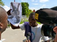 A demonstrator holds up an anti-U.N. poster during an October protest outside a MINUSTAH base in Port-au-Prince. / Credit:Ansel Herz/IPS