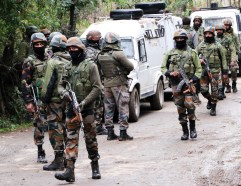 Jammu and Kashmir, Oct 11 (ANI): Security personnel stand guard near an encounter site at Khagund, in Anantnag on Monday. A militant was killed and a policeman injured in an encounter. (ANI Photo)
