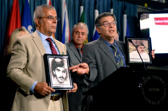 Ahmad Hassani (right) and Mir Garmroud hold photos of their brothers Mahamoud Hassani and Manouchehr Garmroud, both killed in 1988, as members of the Iranian-Canadian community hold a press conference on Parliament Hill in Ottawa, Thursday, Oct. 6, 2016. Photo: Justin Tang