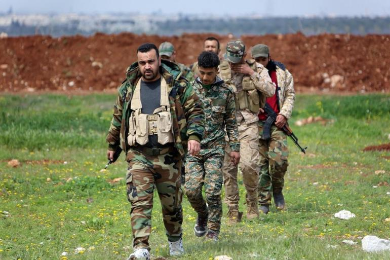 Members of the Syrian government forces march near the town of Qumhanah in the countryside of the central province of Hama, on April 1, 2017 (AFP)